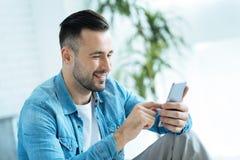 Θετικός απασχολημένος κύριος που χρησιμοποιεί το smartphone στο εσωτερικό Στοκ φωτογραφίες με δικαίωμα ελεύθερης χρήσης