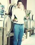 Θετικός αρσενικός πελάτης που έχει τα μπουκάλια του κρασιού στο κατάστημα Στοκ εικόνα με δικαίωμα ελεύθερης χρήσης