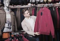 Θετικός αρσενικός πελάτης που εξετάζει τα παλτά Στοκ Φωτογραφίες