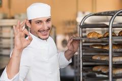 Θετικός αρτοποιός που ελέγχει το πρόσφατα ψημένο ψωμί στοκ φωτογραφία