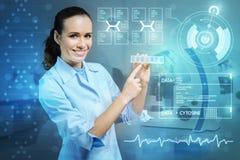 Θετικός ειδικευμένος γιατρός που παρουσιάζει λίγο pillbox και που χαμογελά χαρωπά Στοκ Εικόνες