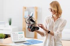 Θετικός ειδικός τεχνολογίας που εξετάζει λίγο ρομπότ στο εσωτερικό Στοκ φωτογραφία με δικαίωμα ελεύθερης χρήσης