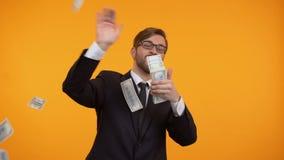 Θετικός επιχειρηματίας που ρίχνει τα τραπεζογραμμάτια δολαρίων στον αέρα, κατανάλωση χρημάτων, επιτυχία απόθεμα βίντεο