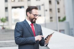 Θετικός επιχειρηματίας που χρησιμοποιεί μια ταμπλέτα υπαίθρια στοκ εικόνες
