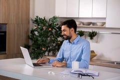 Θετικός επιχειρηματίας που χρησιμοποιεί το lap-top στην κουζίνα στοκ εικόνες