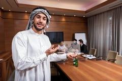 Θετικός ευχαριστημένος Άραβας που κρατά το σχέδιο στοκ εικόνες