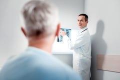 Θετικός ευχαριστημένος γιατρός που έχει τις καλές ειδήσεις στοκ εικόνα