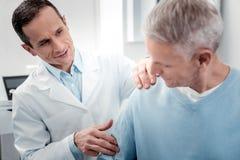 Θετικός ευχαριστημένος γιατρός που κάνει το μασάζ στον ώμο στοκ φωτογραφίες με δικαίωμα ελεύθερης χρήσης