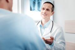 Θετικός ευχαριστημένος γιατρός που υποβάλλει τις ερωτήσεις στοκ εικόνα