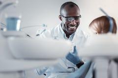 Θετικός ευχαριστημένος διεθνής οδοντίατρος που εξετάζει τον ασθενή του στοκ εικόνες με δικαίωμα ελεύθερης χρήσης