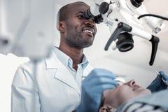 Θετικός ευχαριστημένος διεθνής οδοντίατρος που εξετάζει τον ασθενή του στοκ εικόνα