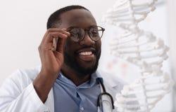 Θετικός ευχαριστημένος επιστήμονας που κρατά τα γυαλιά του στοκ φωτογραφίες