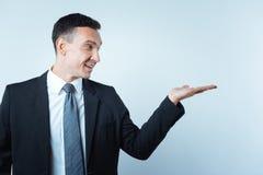 Θετικός ευχαριστημένος επιχειρηματίας που εξετάζει το φοίνικά του στοκ εικόνα