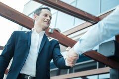 Θετικός ευχαριστημένος επιχειρηματίας που καλωσορίζει το συνάδελφό του στοκ φωτογραφία