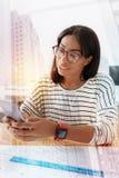 Θετικός ευχαριστημένος εργαζόμενος γραφείων που εξετάζει το τηλέφωνο στοκ φωτογραφία με δικαίωμα ελεύθερης χρήσης
