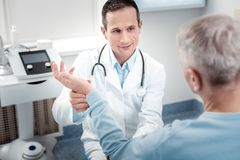 Θετικός ευχαριστημένος ιατρικός εργαζόμενος που ελέγχει το σφυγμό στοκ φωτογραφία