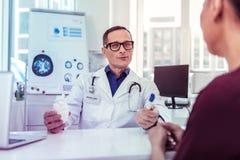Θετικός ευχαριστημένος ιατρικός εργαζόμενος που συμβουλεύεται τον ασθενή του στοκ εικόνες με δικαίωμα ελεύθερης χρήσης