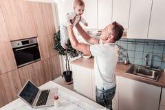 Θετικός ευχαριστημένος μπαμπάς που ανατρέφει το παιδί του στοκ εικόνα