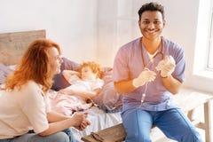 Θετικός ευχαριστημένος νέος γιατρός που κρατά το χαμόγελο στο πρόσωπό του στοκ εικόνα με δικαίωμα ελεύθερης χρήσης