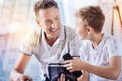 Θετικός ευχαριστημένος νεαρός άνδρας που έχει την ευχάριστη συνομιλία στοκ εικόνες