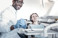 Θετικός ευχαριστημένος οδοντίατρος που εξετάζει το αποστειρωμένο όργανο στοκ φωτογραφία