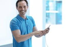 Θετικός ευχαριστημένος πελάτης που χρησιμοποιεί το νέο τηλέφωνο στοκ φωτογραφίες