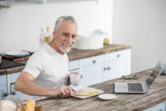 Θετικός ευχαριστημένος συνταξιούχος που έχει το πρόγευμα στοκ εικόνα με δικαίωμα ελεύθερης χρήσης