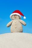 Θετικός δημιουργικός αμμώδης χιονάνθρωπος στο κόκκινο καπέλο Santa στην παραλία Στοκ εικόνες με δικαίωμα ελεύθερης χρήσης