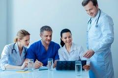 Θετικός ιατρικός εργαζόμενος που εξετάζει τη roentgen εικόνα στοκ φωτογραφίες
