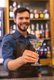 Θετικός μπάρμαν που χαμογελά προσφέροντας το κρύο ποτό οινοπνεύματος στοκ εικόνες
