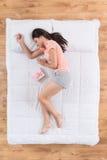 Θετικός νέος ύπνος γυναικών στο κρεβάτι στοκ εικόνες