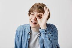 Θετικός νεαρός άνδρας με τις δίκαιες ιδιαίτερες προσοχές τρίχας και χαμόγελο με τη χαρά που παρουσιάζει εντάξει σημάδι που είναι  Στοκ εικόνα με δικαίωμα ελεύθερης χρήσης