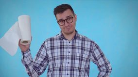 Θετικός νεαρός άνδρας πορτρέτου που στέκεται σε ένα μπλε υπόβαθρο και που κρατά τις πετσέτες εγγράφου απόθεμα βίντεο
