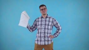 Θετικός νεαρός άνδρας που στέκεται σε ένα μπλε υπόβαθρο και που κρατά τις πετσέτες εγγράφου απόθεμα βίντεο