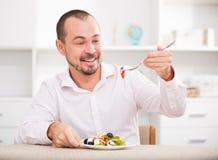 Θετικός νεαρός άνδρας που τρώει την ελληνική σαλάτα στοκ εικόνα με δικαίωμα ελεύθερης χρήσης