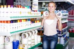 Θετικός πελάτης γυναικών που επιλέγει την κολλητική ταινία στο οικιακό stor Στοκ φωτογραφία με δικαίωμα ελεύθερης χρήσης