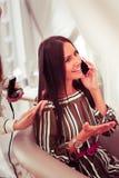 Θετικό ευχαριστημένο κορίτσι brunette που μιλά ανά τηλέφωνο στοκ φωτογραφίες