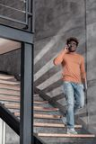 Θετικό ευχαριστημένο νέο αρσενικό που μιλά ανά τηλέφωνο στοκ φωτογραφίες με δικαίωμα ελεύθερης χρήσης