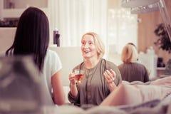 Θετικό ευχαριστημένο ξανθό τσάι κατανάλωσης γυναικών στο σαλόνι στοκ εικόνες με δικαίωμα ελεύθερης χρήσης