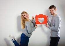 Θετικό ζεύγος με το σπίτι καρδιών Στοκ Φωτογραφία