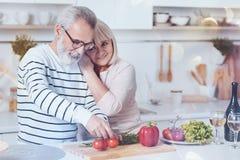 Θετικό ηλικίας lovign ζεύγος που στέκεται στην κουζίνα στοκ εικόνες με δικαίωμα ελεύθερης χρήσης