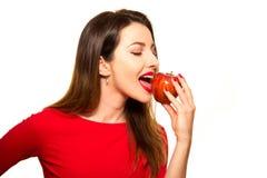 Θετικό θηλυκό που δαγκώνει μεγάλα κόκκινα φρούτα της Apple που χαμογελούν στο άσπρο BA Στοκ εικόνες με δικαίωμα ελεύθερης χρήσης