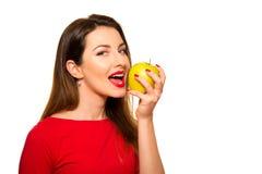 Θετικό θηλυκό που δαγκώνει μεγάλα πράσινα φρούτα της Apple που χαμογελούν στο λευκό Στοκ φωτογραφία με δικαίωμα ελεύθερης χρήσης