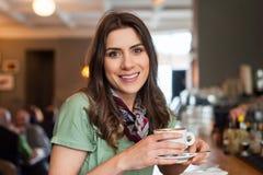 Θετικό κορίτσι που παίρνει μια συνεδρίαση σπασιμάτων στο φραγμό στο κατάστημα καφέδων στοκ εικόνα