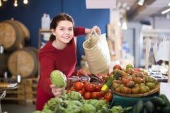 Θετικό νέο κορίτσι που φαίνεται αγκινάρες στην αγορά στοκ φωτογραφία με δικαίωμα ελεύθερης χρήσης