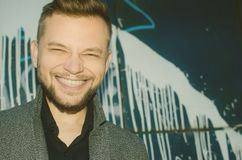 Θετικό χαμογελώντας άτομο στο υπόβαθρο ενός χρωματισμένου τοίχου τονισμένος Στοκ Εικόνα
