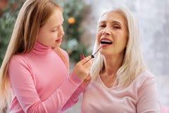 Θετικό χαριτωμένο κορίτσι που βάζει στο makeup Στοκ Εικόνες