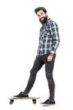 Θετικό hipster γέλιου με να διαπερνήσει smiley που στέκεται skateboard στην πλάγια όψη Στοκ φωτογραφία με δικαίωμα ελεύθερης χρήσης