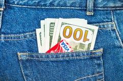 Θεώρηση πιστωτικών καρτών με τα αμερικανικά δολάρια που κολλούν από τα πίσω τζιν Στοκ Εικόνες