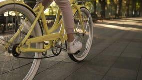 Θηλυκά απρόσωπα πόδια που περπατούν με το ποδήλατο στο στρωμένο ενεργό τρόπο ζωής οδικής κοντά επάνω πλάγιας όψης Η γυναίκα κοριτ φιλμ μικρού μήκους